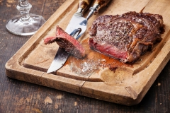 Steak Ribeye with knife and fork for meat on cutting board on dark wooden background